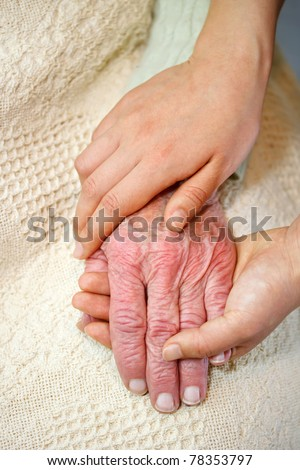 Old and Young Hands on White Blanket - stock photo