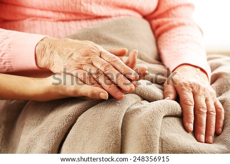 Old and young holding hands, closeup - stock photo