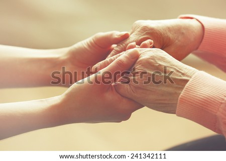 Old and young holding hands on light background, closeup - stock photo