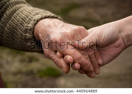 Old and young person holding hands. Elderly care and respect