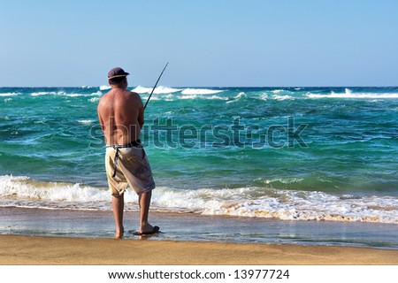 Old angler on sunset beach. Shot in Sodwana Bay Nature Reserve, KwaZulu-Natal province, Southern Mozambique area, South Africa. - stock photo