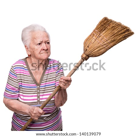 Old angry woman threatening with a broom on a white background - stock photo