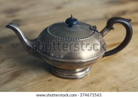 old antigue teapot on a wooden table - stock photo