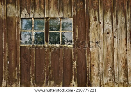 Old antique barn with double window panes reflecting trees in field. Barn is over one hundred years old. /Old antique weathered barn with windows reflecting tree - stock photo