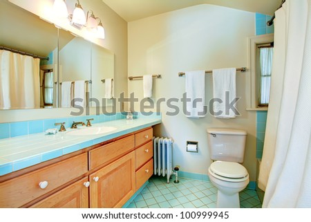 Old antique bathroom with blue tiles and white shower. - stock photo