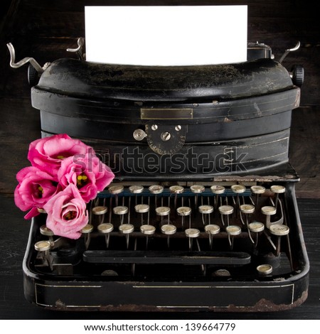 Old antique black vintage typewriter and empty paper for copy space, with red romantic flowers - stock photo