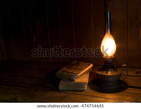 Old antique books with burning paraffin lamp near on the wooden table.