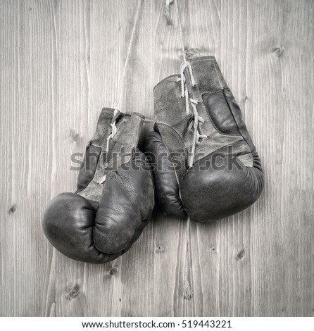 Old antique boxing gloves hanging against wooden wall / door.