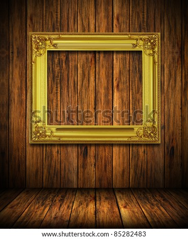 Old antique gold frame on wood wall room background - stock photo