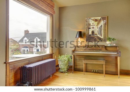 Old antique piano and living room with the view of the English house. - stock photo