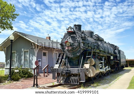 Old antique  railroad steam engine by train station. - stock photo