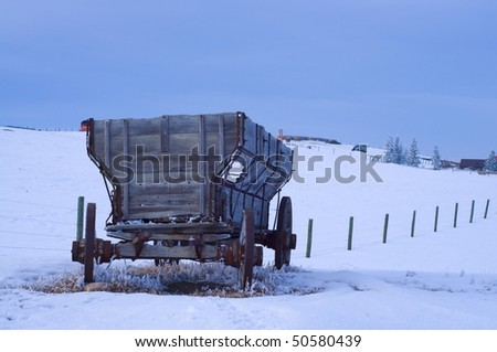 Old Antique Wagon in snow covered field - stock photo