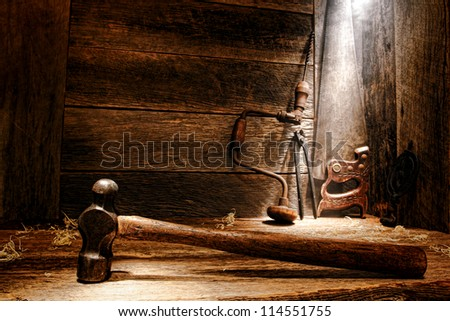 Old antique wood handle blacksmith hammer and used antique carpenter tools with ancient manual drill and crosscut saw in vintage wood working carpentry workshop lit by soft diffused light through dust