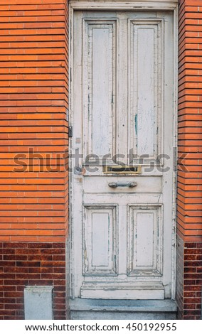Old antique worn white wooden door with red brick wall. Vintage effect.   - stock photo