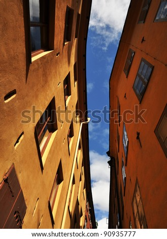 Old apartment buildings against blue sky - stock photo