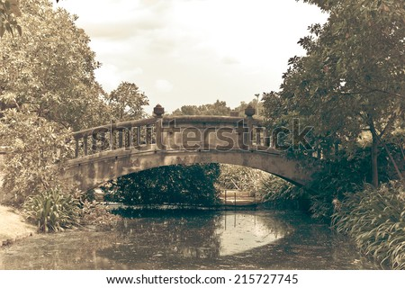 old arch bridge over the canal, vintage photo style processed - stock photo