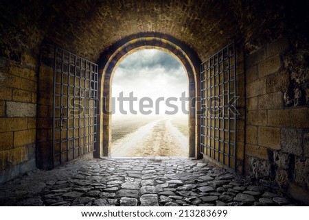 Old Arch Gate opening to endless country road leading nowhere. Hopelessness and great unknown concept. - stock photo