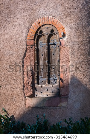 Old arched gateway in a wall in the Alsace village of Obernai, France - stock photo