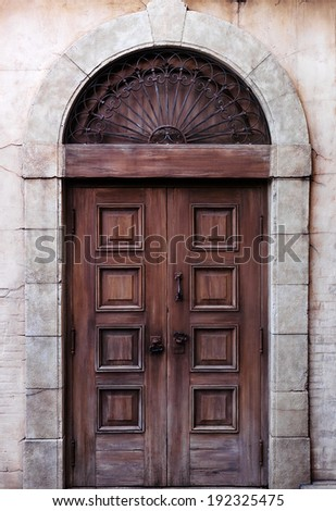 Old arched wooden door rustic vintage architectural detail texture - stock photo
