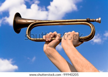 Old army trumpet in hand over blue sky - stock photo