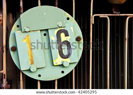 Old Army vehicle identification plate. License plate number sixteen. - stock photo