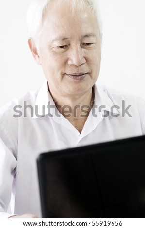 old asian business man surfing with a laptop