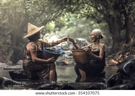 Old Asian woman working in cascade, Thailand - stock photo
