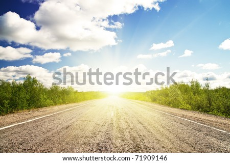 Old asphalt road in green meadow. Russia. Sunset