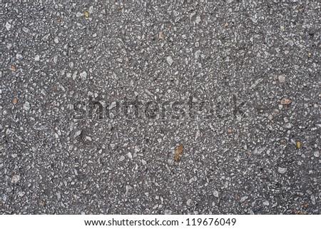 Old asphalt road with big grain stones. - stock photo