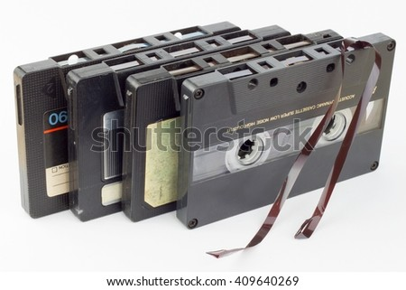 Old audio cassette isolated on white. Dusty damaged audio cassette, historical sound recording on magnetic tape. Place for your text. - stock photo