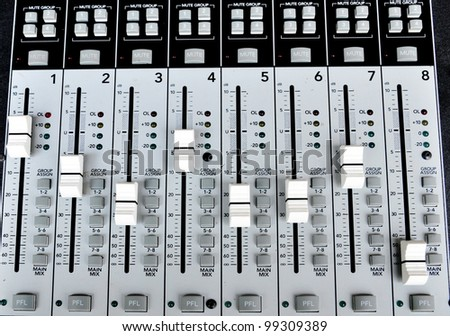old audio mixing board with multiple channel faders and adjusting knobs - stock photo