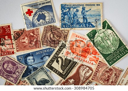 Old Australian Stamps - 1960s:[A small selection of old, used, and circulated Australian stamps. Subjects captured against soft window lighting on white bond paper background.] - stock photo