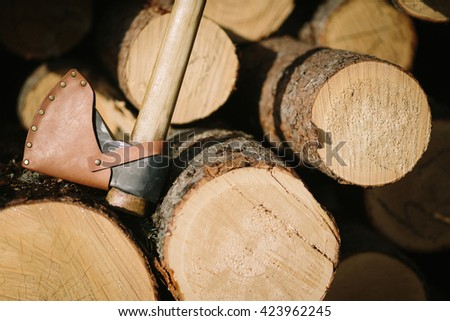 Old axe in log on a firewood background