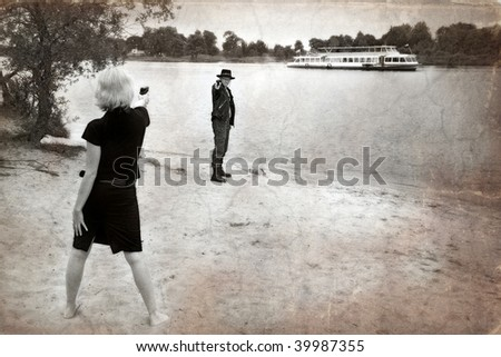 old b&w photo of woman pointing gun at man wearing cowboy hat, river and ship in background - stock photo