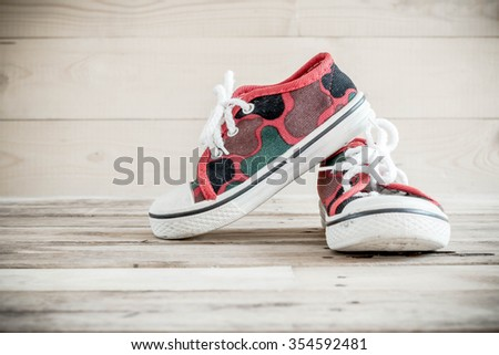 Old baby shoes on wooden background. - stock photo