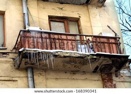 old balcony with icicles in city