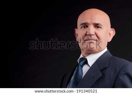 old bald self-confident businessman on a dark background - stock photo