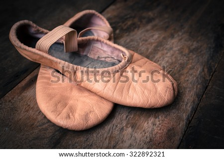 Old ballet shoes on old wooden floor.