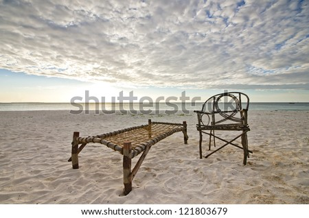 Old Bamboo Chair and Camp Bed Sitting on Sandy Beach with Sea and Setting Sun Over Dramatic Sky. - stock photo