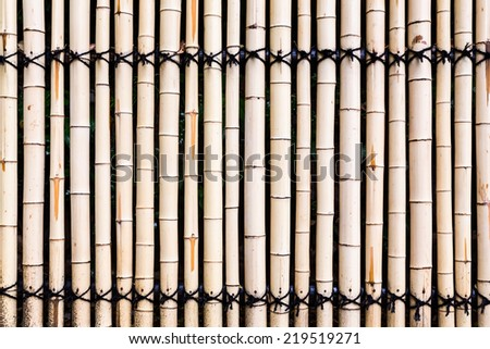 Old bamboo fence background with rope - stock photo