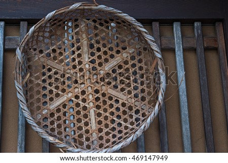 old bamboo wicker basket on the old wooden wall, background