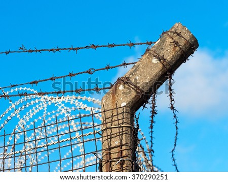 old barbed wire fence in bright sunlight - stock photo