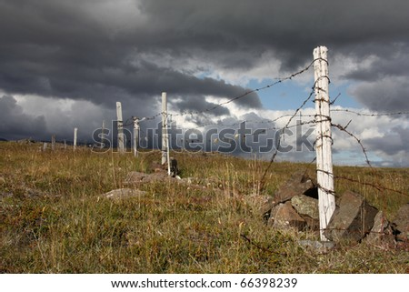 Old barbed wire fence in mountains of Iceland - stock photo