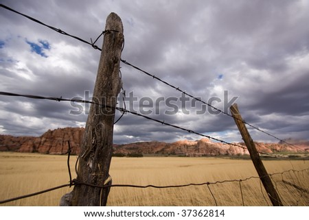 Old barbed wire fence with wheat field, cliffs and storm clouds in background. - stock photo