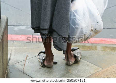 Old bare-legged Homeless man with a bag of rubbish. - stock photo