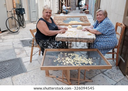 "OLD BARI, ITALY - JULY 06: mother and daughter working the dough to make fresh pasta in the street Arco Basso of Old Bari, also known as the street of ""orecchiette"". Shot in 2015 - stock photo"