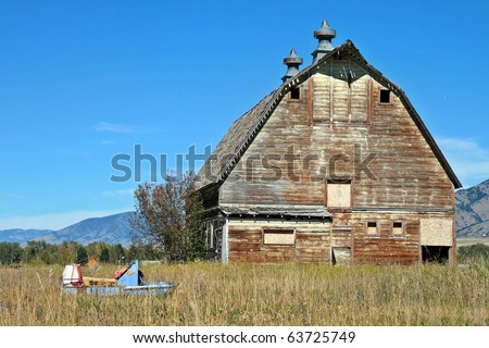 Old Barn against a blue sky with a broken snowmobile in a field - stock photo