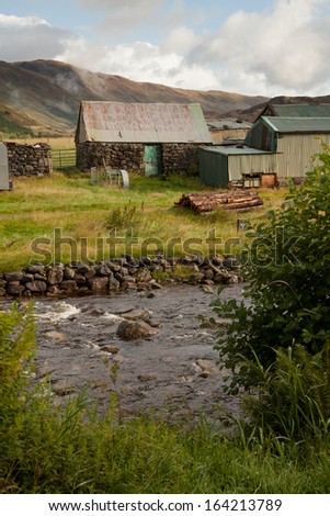 Old barn along a stream in the Scottish Highlands. - stock photo