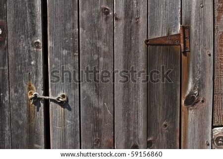 Old barn door closed with a hook.