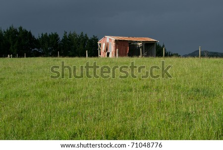 Old barn in sunlight with approaching storm in the background - stock photo